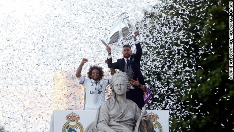 Real Madrid's defender Sergio Ramos (R) holds up the trophy beside Real Madrid's Brazilian defender Marcelo celebrating the team's win on Plaza Cibeles in Madrid on June 4, 2017 after the UEFA Champions League football match final Juventus vs Real Madrid CF held at the National Stadium of Wales in Cardiff on June 3, 2017. / AFP PHOTO / OSCAR DEL POZO        (Photo credit should read OSCAR DEL POZO/AFP/Getty Images)