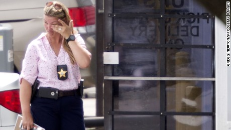 A law enforcement official wipes her eyes at the entrance to the shooting crime scene in Orlando, Florida on Monday.