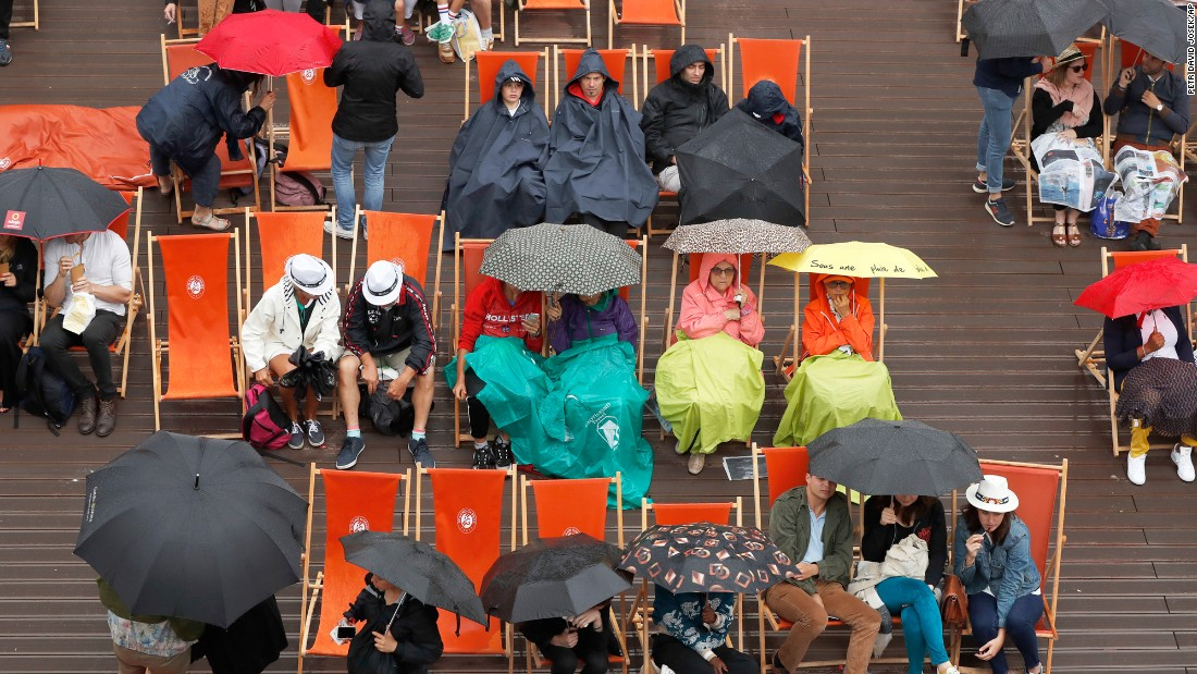 Spectators break out their umbrellas after French Open play was suspended because of rain on Saturday, June 3.