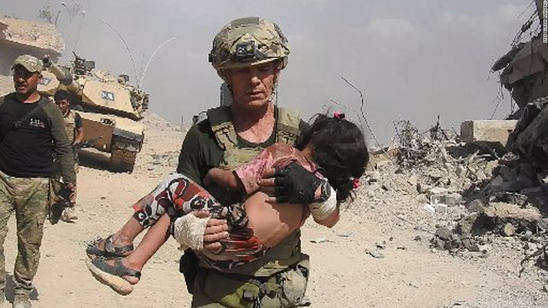 "Dave Eubank from the ""Free Burma Rangers"" volunteer organization carries a little girl to safety after spotting her hiding under her dead mother's hijab for two days. The child was rescued in western Mosul as gunfire raked the area. Photo courtesy of Free Burma Rangers (www.freeburmarangers.org/)"