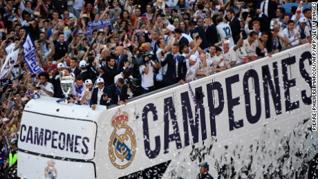 Real Madrid football team fans surround the bus as Real Madrid players hold up the trophy celebrating the team's win on Plaza Cibeles in Madrid on June 4, 2017 after the UEFA Champions League football match final Juventus vs Real Madrid CF held at the National Stadium of Wales in Cardiff on June 3, 2017. / AFP PHOTO / PIERRE-PHILIPPE MARCOU        (Photo credit should read PIERRE-PHILIPPE MARCOU/AFP/Getty Images)