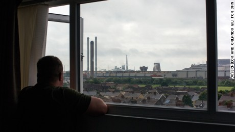 Carl Cerasuolo, 36, looks out of his son's bedroom window onto the TATA Steel works. Karl worked at the plant for 11 years before being made redundant. He now works as a children's care worker.