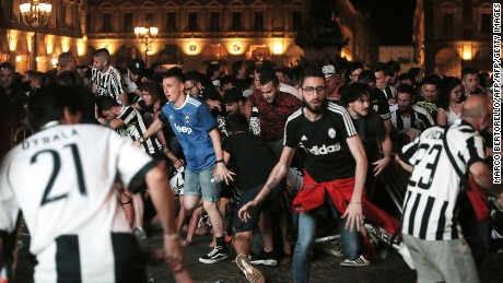 Juventus' supporters evacuate the Piazza San Carlo after a panic movement in the fanzone where thousands of Juventus fans watched the UEFA Champions League Final football match between Juventus and Real Madrid on a giant screen, on June 3, 2017 in Turin.  / AFP PHOTO / Marco BERTORELLO        (Photo credit should read MARCO BERTORELLO/AFP/Getty Images)