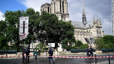 French police officers gather at a cordonned-off area at the Notre-Dame cathedral.