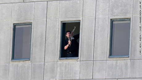 An armed man stands in a window of the parliament building in Tehran, Iran, Wednesday, June 7, 2017. Several attackers stormed into Iran's parliament and a suicide bomber targeted the shrine of Ayatollah Ruhollah Khomeini on Wednesday, killing a security guard and wounding several other people in rare twin attacks, with the shooting at the legislature still underway.