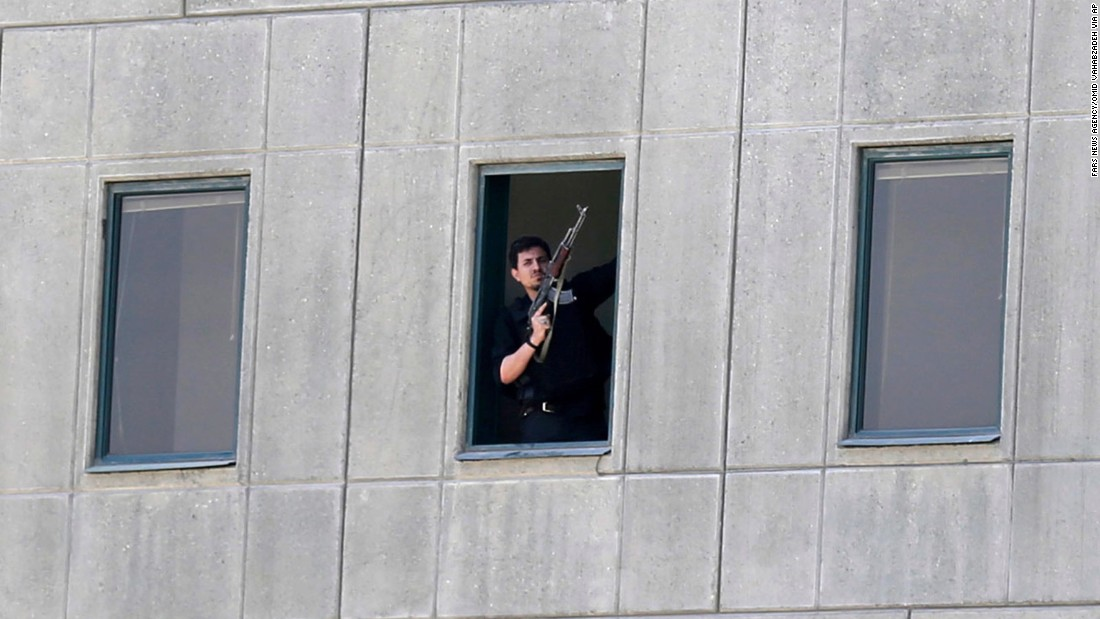 An armed security officer stands in a window of the parliament building during the attack.
