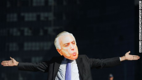 A member of the global web movement Avaaz with a mask of Brazilian President Michel Temer demonstrates in front of the Supreme Electoral Court (TSE) requesting the key partner of his center-right alliance in Congress, the PSDB party, to leave him, in Brasilia on June 7, 2017 as the PSDB holds a session examining whether the 2014 reelection of president Dilma Rousseff and her then-vice president Temer should be invalidated because of corrupt campaign funding. Judges on Brazil's electoral court were expected to start voting Wednesday in a case that could topple scandal-tainted President Michel Temer. If the court votes to scrap the election result, Temer -- who took over only last year when Rousseff was impeached -- would himself risk losing his office.  / AFP PHOTO / Andressa Anholete        (Photo credit should read ANDRESSA ANHOLETE/AFP/Getty Images)