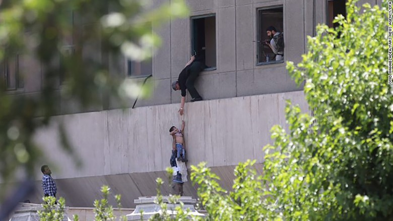 An Iranian police officer helping people flee parliament during an attack in Tehran, Iran, on Wednesday.