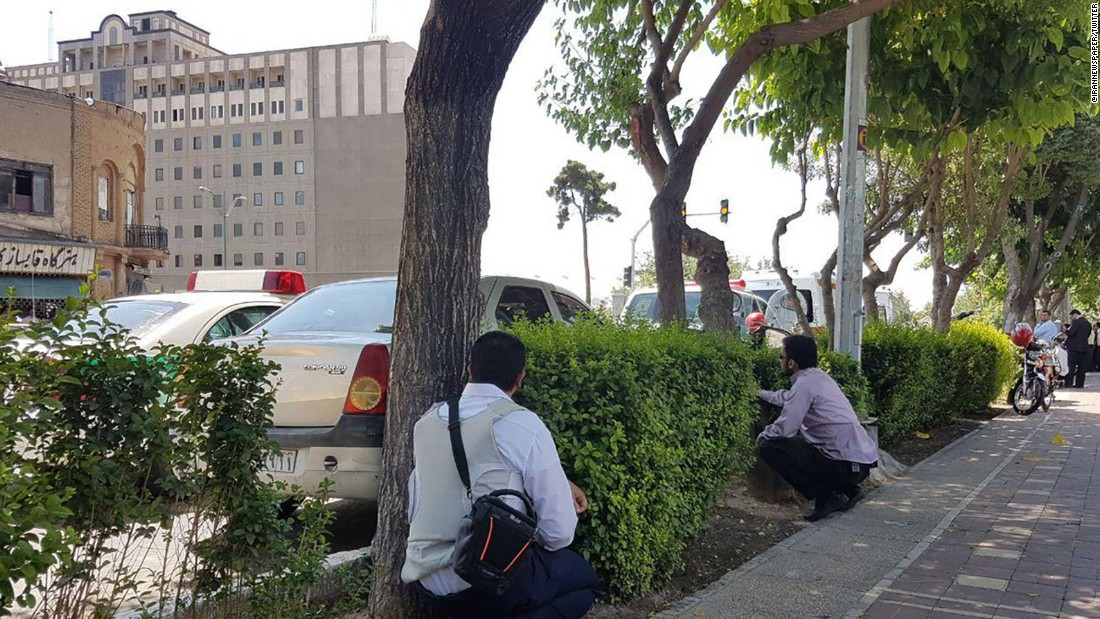 People duck behind shrubs during attacks Wednesday in and near Tehran.