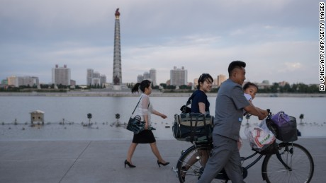North Koreans walk past the Juche Tower in Pyongyang. The country has criticized Trump's decision to withdraw from the Paris climate agreement.