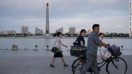 In a photo taken on June 4, 2017 a man pushes a child on a bicycle past the Juche tower and Taedong river in Pyongyang. / AFP PHOTO / Ed JONES        (Photo credit should read ED JONES/AFP/Getty Images)