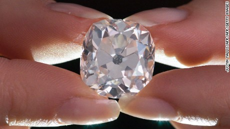 A member of Sotheby's staff poses holding a 26.27 carat, cushion-shaped, white diamond, for sale at Sotheby's auction house in London on May 22, 2017. The large diamond is expected to fetch around 350,000 GBP (405,000 euro; 456,000 USD) at auction 30 years after its owner paid 10 GBP for it at a car boot sale, thinking it was a costume jewel. / AFP PHOTO / Justin TALLIS        (Photo credit should read JUSTIN TALLIS/AFP/Getty Images)
