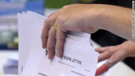 A counting staff member sorts ballots from postal votes at the Meadowbank Sports Centre counting centre in Edinburgh, Scotland,  on June 8, 2017, as Britain votes in a general election.   Britons streamed to the polls in the last few hours of a snap general election on June 8 after a campaign dominated by terror attacks and the uncertainty of Brexit. / AFP PHOTO / Lesley Martin        (Photo credit should read LESLEY MARTIN/AFP/Getty Images)