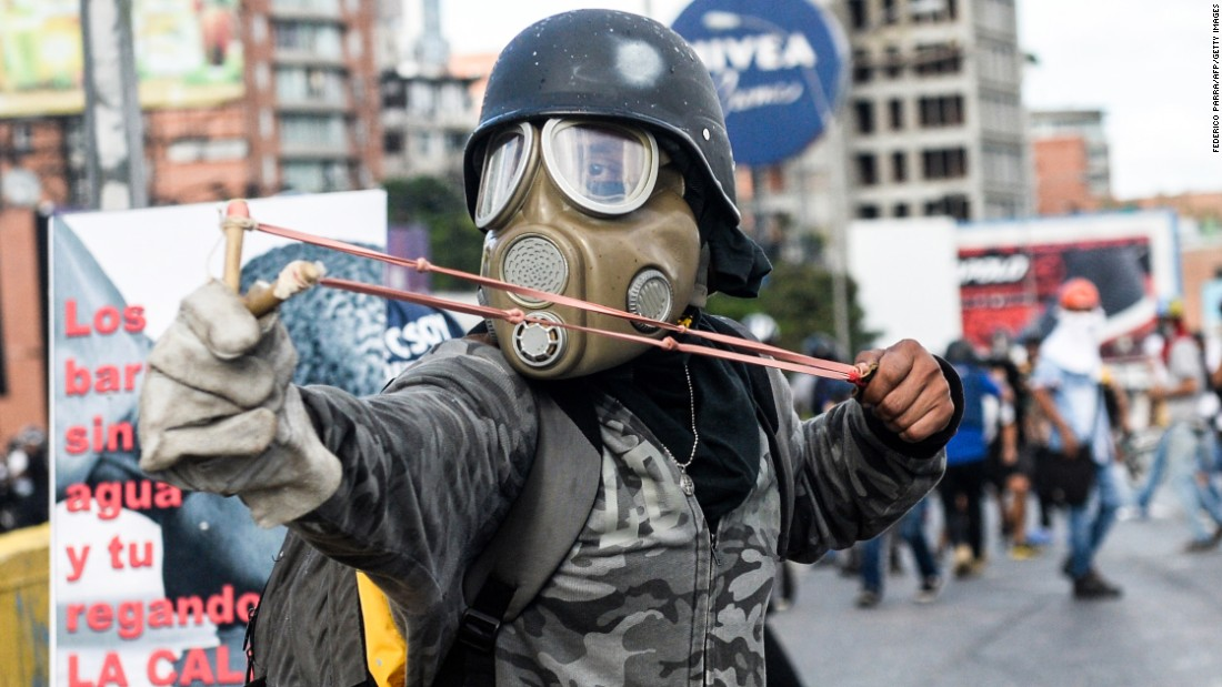 "An activist uses a slingshot in clashes with riot police during anti-government protests in Caracas, Venezuela, on Saturday, June 10. The country <a href=""http://www.cnn.com/2017/05/09/americas/venezuela-violin-protester/"" target=""_blank"">has witnessed widespread unrest</a> since March 29, when the Venezuelan Supreme Court dissolved Parliament and transferred all legislative powers to itself. Though the decision was reversed three days later, protests continue across the country, which is in the midst of an economic crisis."