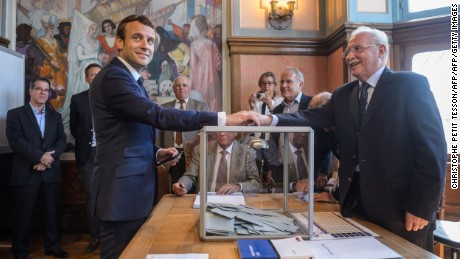French President Emmanuel Macron (L) casts his ballot at a polling station to vote in the first round of the French legislative elections in Le Touquet, on June 11, 2017.  / AFP PHOTO / POOL / Christophe Petit Tesson        (Photo credit should read CHRISTOPHE PETIT TESSON/AFP/Getty Images)