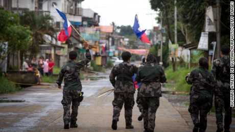 The Philippine National Police hang flags in war-torn Marawi City  to boost troop morale.