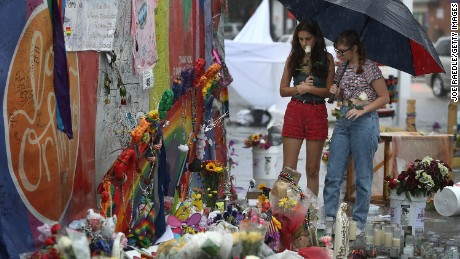 Madison Fisher and Sarah Partenio (L-R) visit the memorial to the victims of the mass shooting setup around the Pulse gay nightclub one day before the one year anniversary of the shooting on June 11, 2017 in Orlando, Florida. Omar Mateen killed 49 people at the club a little after 2 a.m. on June 12, 2016.