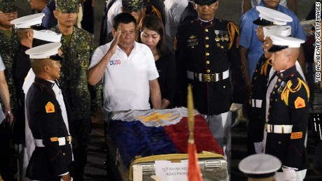 Philippine President Rodrigo Duterte (C) salutes in front of a flag-draped casket of a slain marine at a military base in Manila on June 11.
