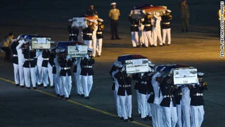 Philippine marines honour guards carry the caskets containing the bodies of their colleagues killed last June 9 in Marawi, shortly after arriving at a military base in Manila on June 11.
