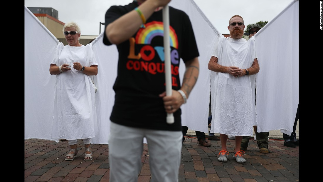 "People dressed as ""guardian angels"" attend the memorial service."