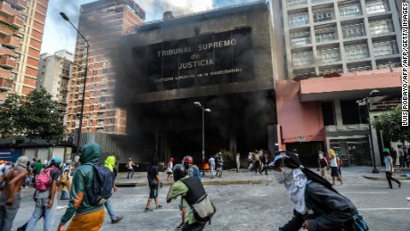Anti-government demonstrators attack the administration headquarters of the Supreme Court of Justice as part of protests against President Nicolas Maduro in Caracas, on June 12, 2017.  With Venezuelans suffering from high inflation, food shortages and soaring crime rates, plus a deepening corruption scandal, the Venezuelan opposition has mounted near-daily anti-government protests since April 1. The protests have left 66 dead and more than a thousand injured, according to prosecutors.   / AFP PHOTO / LUIS ROBAYO        (Photo credit should read LUIS ROBAYO/AFP/Getty Images)