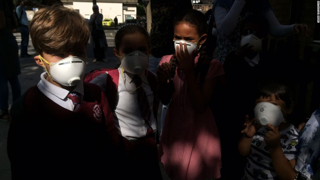 Children wear masks that were distributed near the site of the fire.
