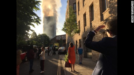 Londoners commuting to work watch the smoldering tower Wednesday morning.