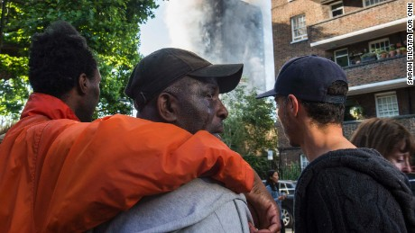 People comfort a man whose relatives lived in Grenfell Tower and hadn't yet been located since the fire.