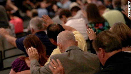 People pray during the Southern Baptist Convention annual meeting, Tuesday, June 13, 2017, in Phoenix. (AP Photo/Matt York)