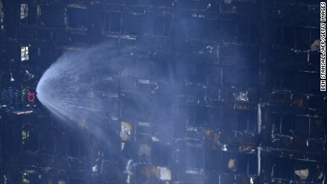 TOPSHOT - Firemen spray water onto the facade of the Grenfell Tower after a fire ripped through the building in west London on June 14, 2017. At least six people were killed Wednesday when a massive fire tore through a London apartment block overnight, with survivors voicing anger over longstanding safety fears at the 24-storey Grenfell Tower. / AFP PHOTO / Ben STANSALL        (Photo credit should read BEN STANSALL/AFP/Getty Images)