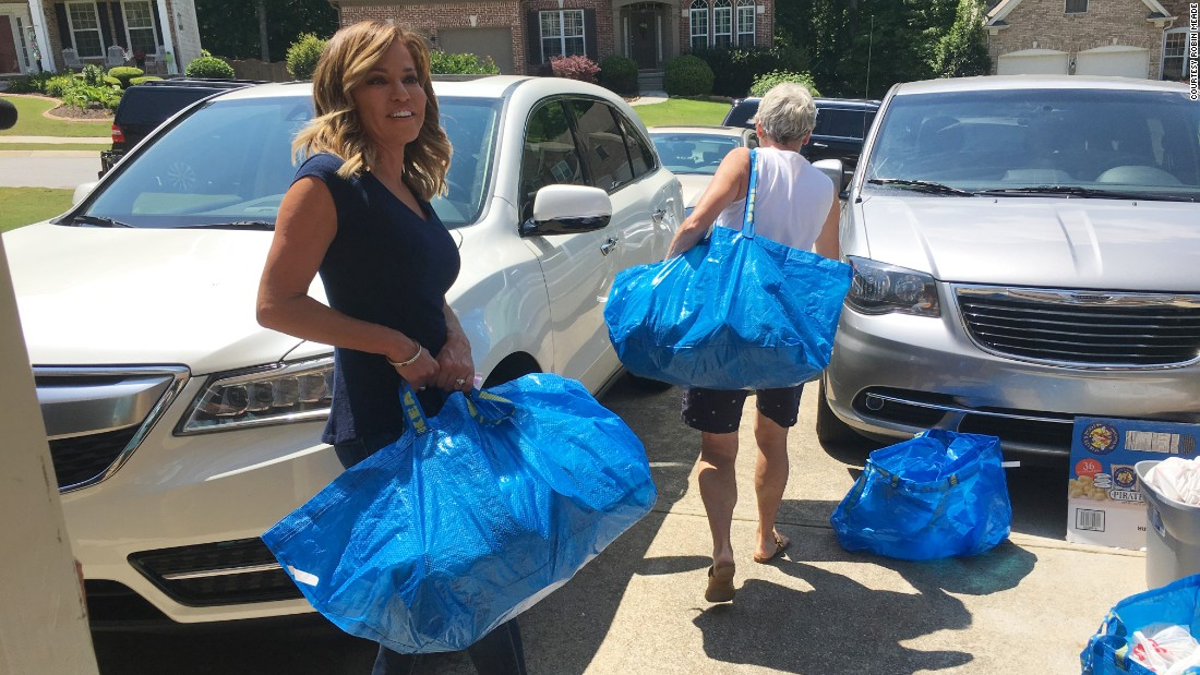 Meade carries bags during a volunteer effort with the Blessings in a Backpack organization.