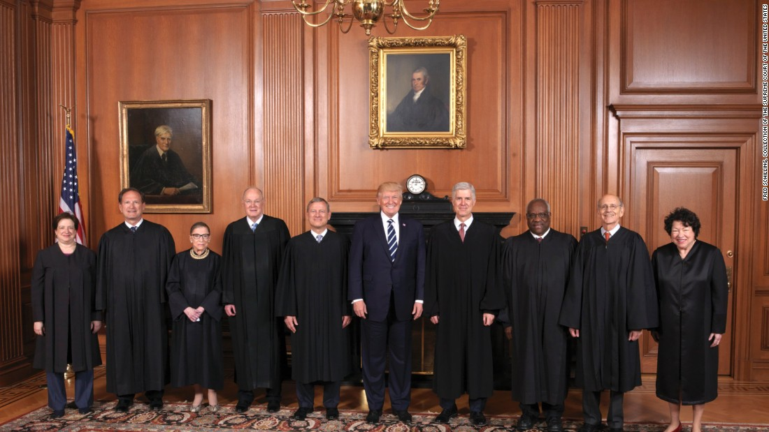 Trump stands with the Supreme Court at Gorsuch's formal investiture ceremony in June 2017. From left are Elena Kagan, Samuel Alito, Ruth Bader Ginsburg, Kennedy, Chief Justice John Roberts, Trump, Gorsuch, Clarence Thomas, Stephen Breyer and Sonia Sotomayor.