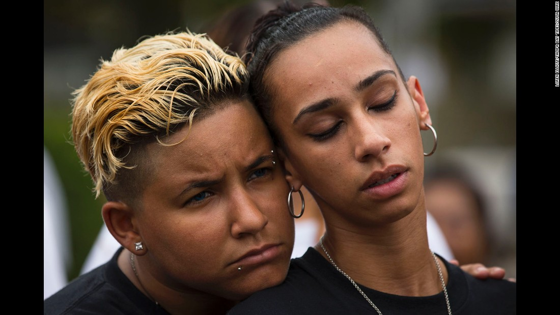 "Angel Ayala, left, and her girlfriend, Carla Montanez, attend a memorial service at the Pulse nightclub in Orlando on Monday, June 12. <a href=""http://www.cnn.com/2017/06/12/us/gallery/pulse-memorial/index.html"" target=""_blank"">A vigil was held at the club</a> a year after a mass shooting claimed 49 lives there."