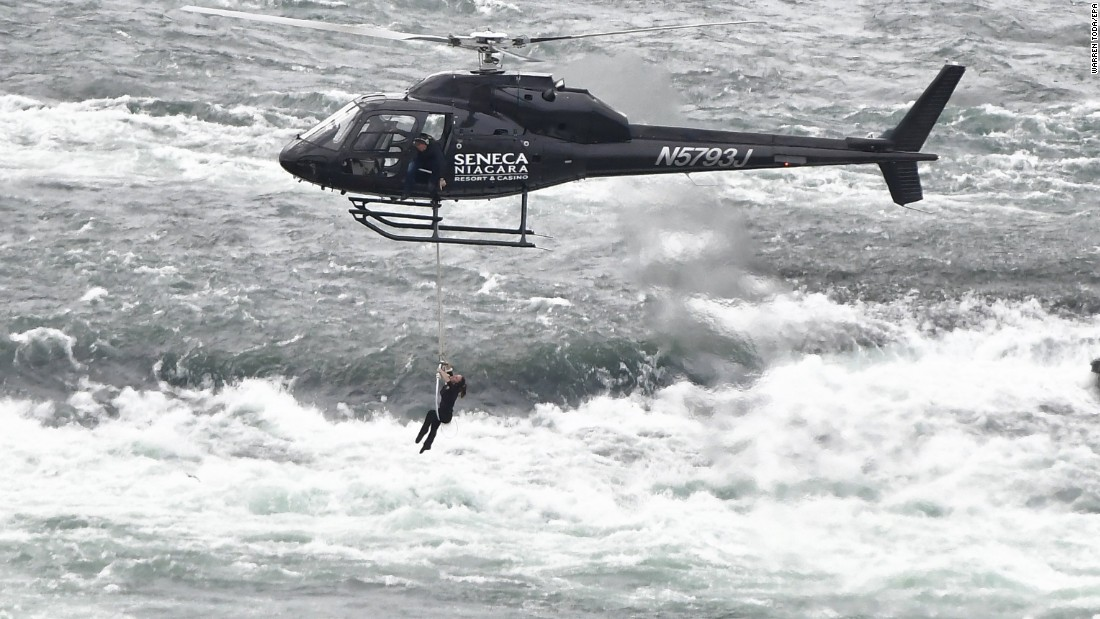Acrobat Erendira Wallenda hangs above the Niagara River in Niagara Falls, New York, on Thursday, June 15. At one point she even hung on by her teeth. Watching from the helicopter is her husband, daredevil Nik Wallenda.