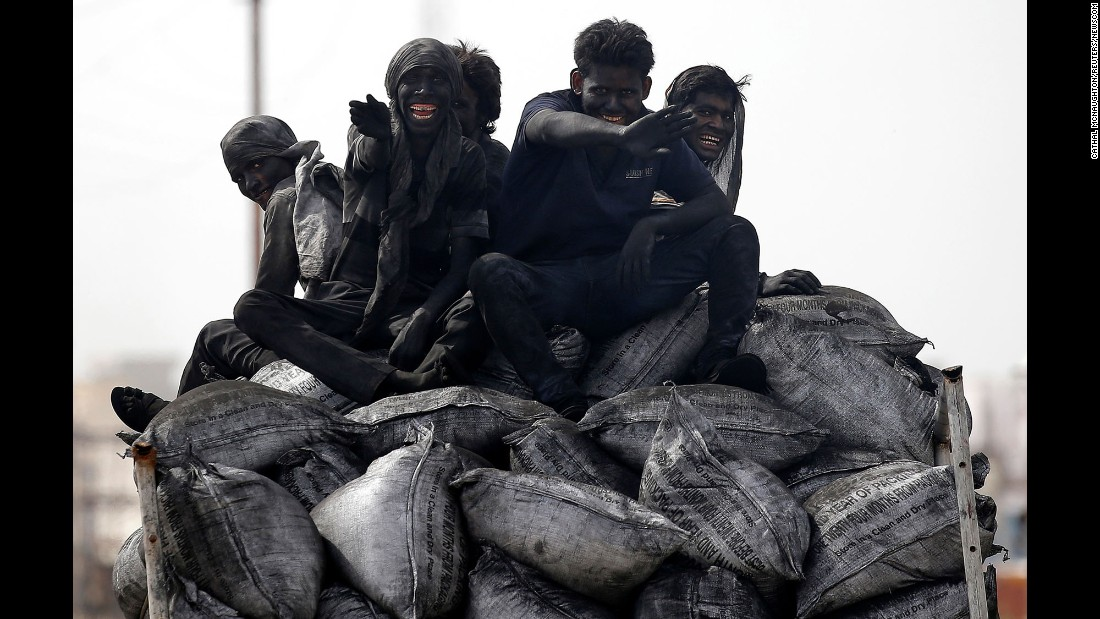 Coal workers ride on the back of a truck in Barsana, India, on Tuesday, June 13.