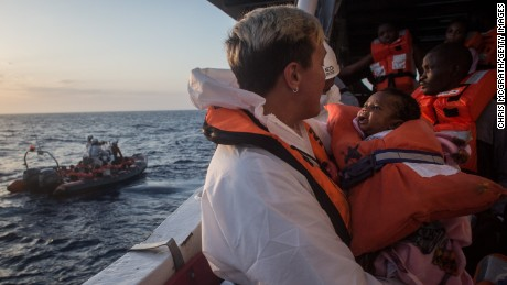 A crewmember from the Migrant Offshore Aid Station (MOAS) Phoenix vessel holds a child as they wait to transfer refugees and migrants to a waiting Italian coastguard ship after being rescued at sea off Lampedusa, Italy.