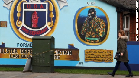 A woman walks past a loyalist mural, depicting an Ulster Freedom Fighter (UFF) in Belfast.