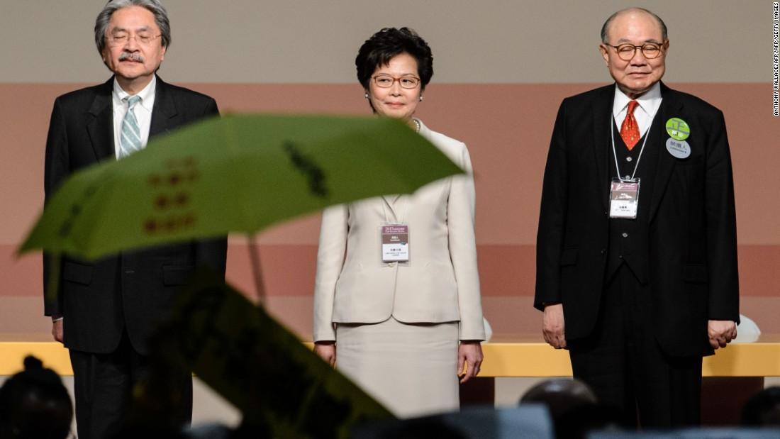 Carrie Lam (center) stands on stage after being selected to be the next Hong Kong Chief Executive on March 26, 2017. In the foreground, a yellow umbrella is unfurled to protest the undemocratic nature of the race Lam won.