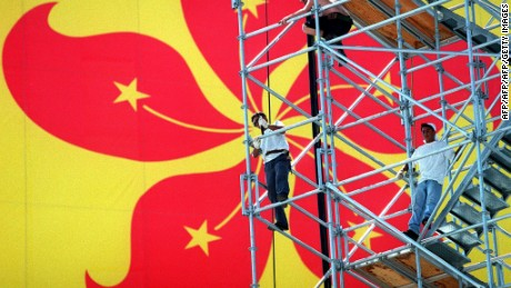 Framed by Hong Kong's new symbol, the Bauhinia flower, workers set up viewing platforms for the British Farewell Ceremony 21 June. Dragons, dancers and drummers are among the more than 2,000 cast members taking part in the ceremony June 30, which will include an address by His royal Highness The Prince of Wales.  AFP PHOTO/Stephen SHAVER (Photo credit should read STEPHEN SHAVER/AFP/Getty Images)
