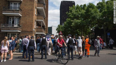 A crowd gathers in view of the blackened Grenfell Tower.