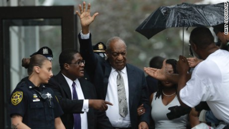Bill Cosby gestures while exiting the Montgomery County Courthouse with his publicist Andrew Wyatt, second from left, after a mistrial was declared in his sexual assault trial in Norristown, Pennsylvania on Saturday, June 17, 2017. Cosby's trial ended without a verdict after jurors failed to reach a unanimous decision.