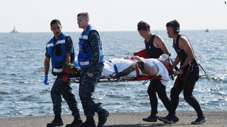An injured USS Fitzgerald crew member is carried by US military personnel, left, and Japanese Maritime Self-Defense Force members upon arriving Saturday to the US Naval Base in Yokosuka Japan.