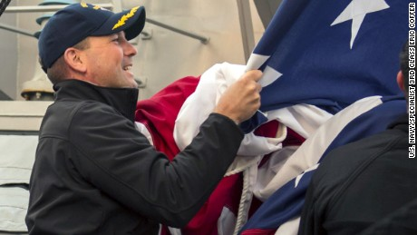 The USS Fitzgerald's captain, Cmdr. Bryce Benson, assists in bringing down the battle ensign on board the guided-missile destroyer USS Fitzgerald on March 22.