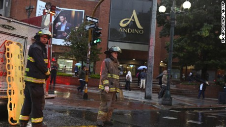 Firefighters stand outside the Centro Andino shopping center in Bogota, Colombia, Saturday, June 17, 2017. A explosion rocked the mall, one of the busiest in Colombia's capital, killing at least one woman and injuring 11 others according to authorities. (AP Photo/Ricardo Mazalan)