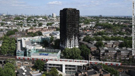 A Tube train passes the remains of Grenfell Tower in June.