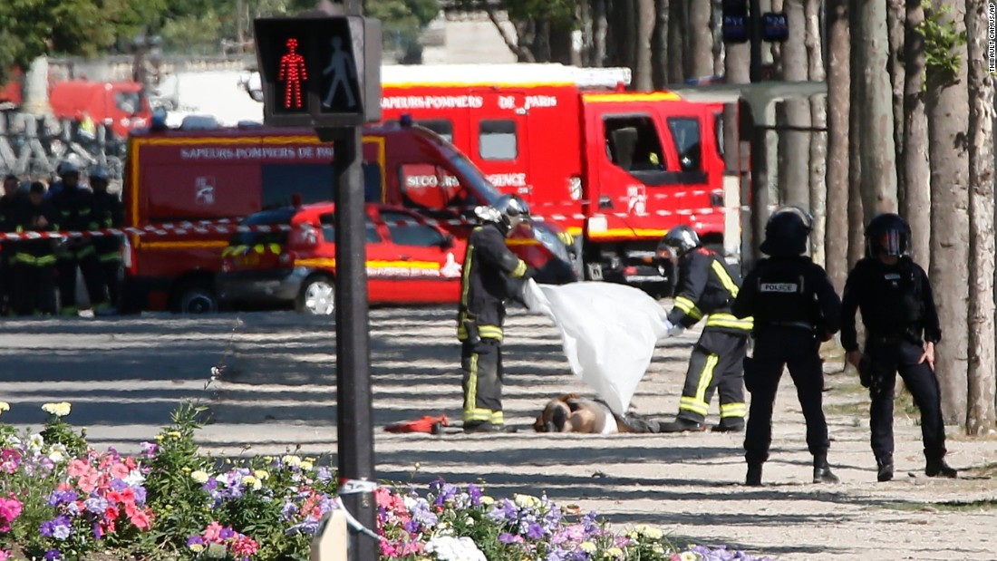 Rescue workers cover the suspect's body on the Champs-Elysees.
