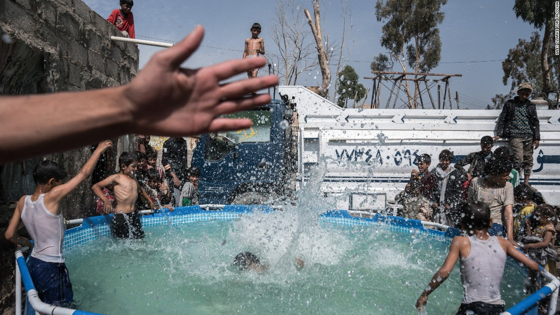 Children play in a pool of water in the Harat Al-Masna'a slum in Sana'a. The slum, which is close to an urban military base, was hit by two airstrikes last year on the Eid Al-Adha holiday, destroying 25 houses.
