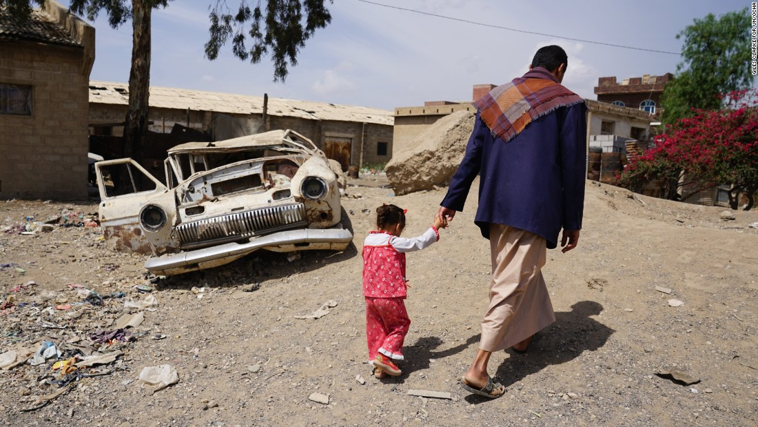 Abdellatif Allami walks with his three-year-old daughter Sara in the Harat Al-Masna'a slum in Sana'a, home to the families of former factory workers. They used to receive a basic pension of around $120 a month, but the payments stopped seven months ago, and the families now rely on donations to survive.