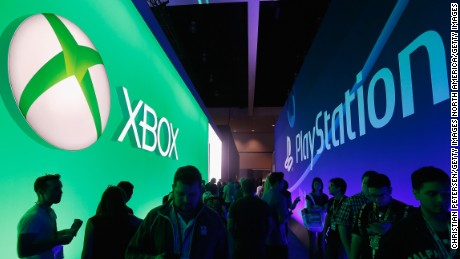 LOS ANGELES, CA - JUNE 16:  Game enthusiasts and industry personnel walk between the Microsoft XBox and the Sony PlayStation exhibits at the Annual Gaming Industry Conference E3 at  the Los Angeles Convention Center on June 16, 2015 in Los Angeles, California. The Los Angeles Convention Center will be hosting the annual Electronic Entertainment Expo (E3) which focuses on gaming systems and interactive entertainment, featuring introductions to new products and technologies.  (Photo by Christian Petersen/Getty Images)