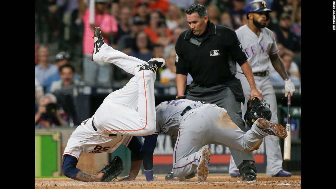 Houston pitcher Francis Martes, left, tumbles over Texas' Jonathan Lucroy as Lucroy scores on a wild pitch on Wednesday, June 14.
